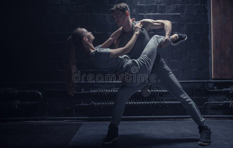 执行在黑暗的专业舞蹈家点燃了室 库存照片