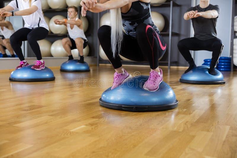 执行在Bosu球的朋友蹲锻炼在健身房 图库摄影