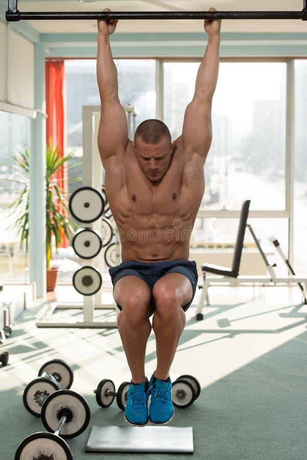 执行垂悬的腿的年轻人提高吸收锻炼 图库摄影
