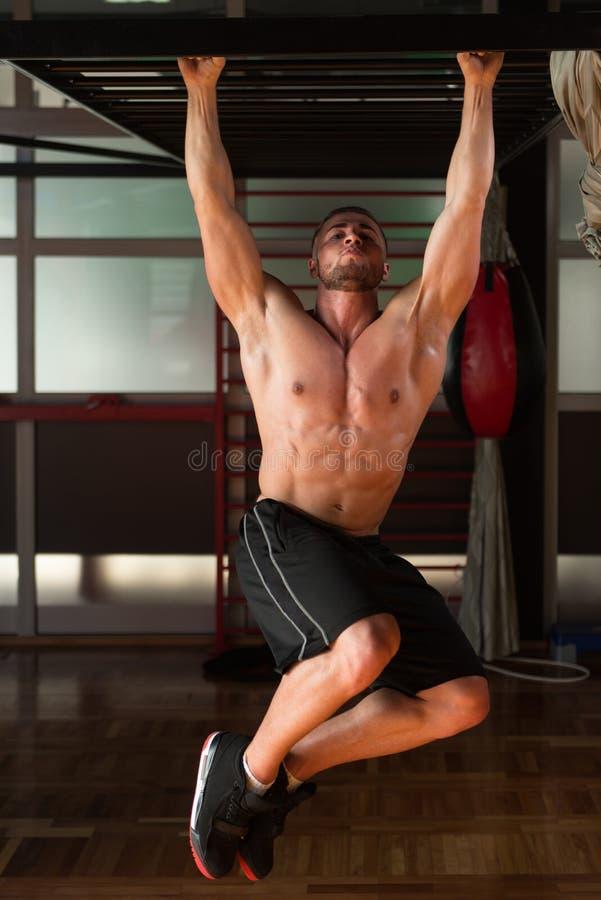 执行垂悬的腿的年轻人提高吸收锻炼 免版税库存图片