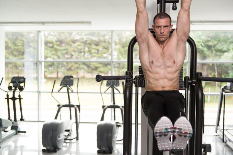 执行垂悬的腿的年轻人提高吸收锻炼 免版税图库摄影