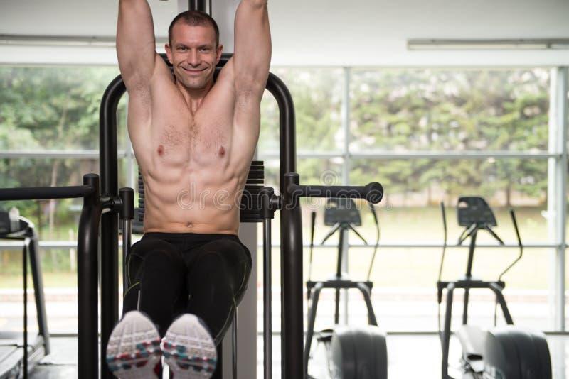 执行垂悬的腿的年轻人提高吸收锻炼 免版税库存照片