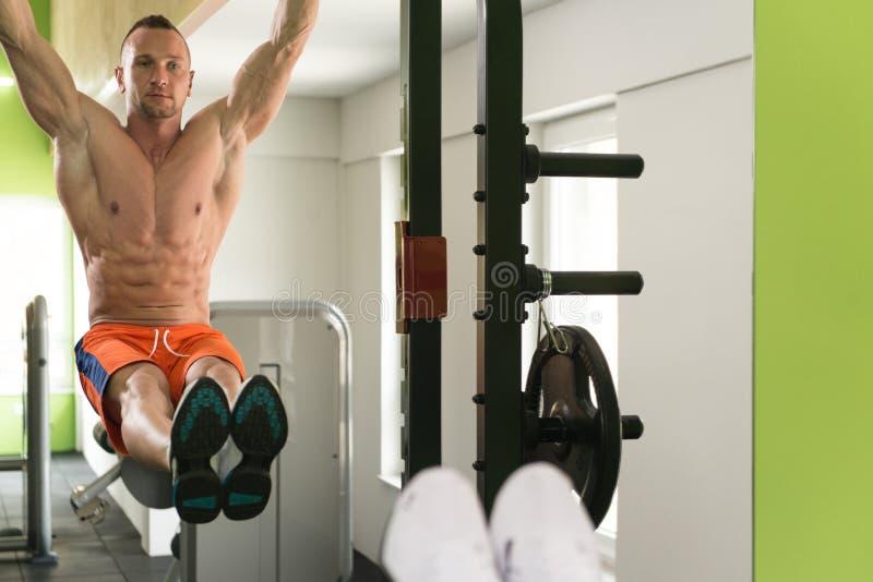 执行垂悬的腿的年轻人提高锻炼 图库摄影