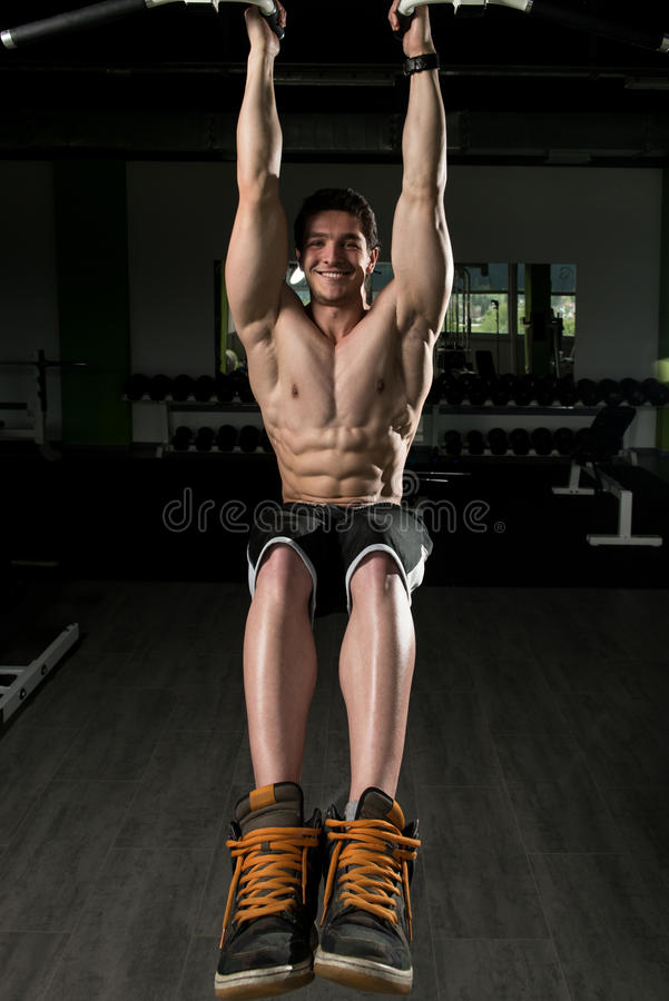 执行垂悬的腿的年轻人提高锻炼 库存图片