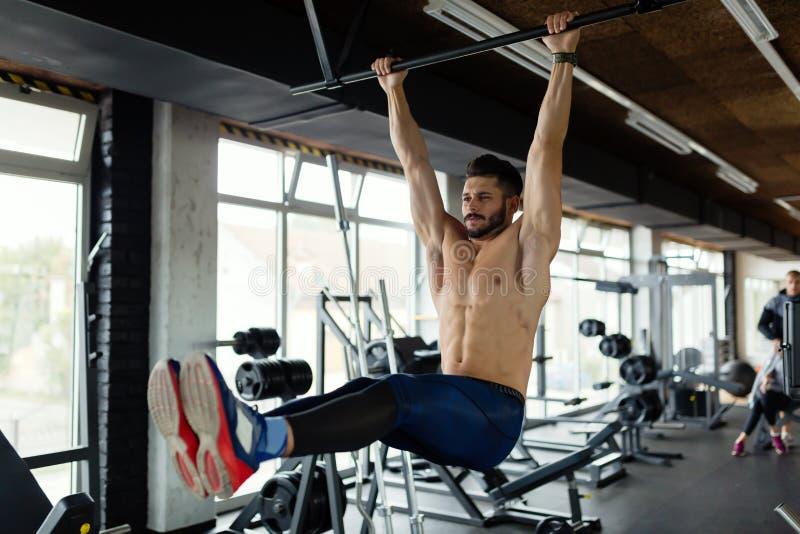 执行垂悬的腿的年轻人提高锻炼 免版税库存图片