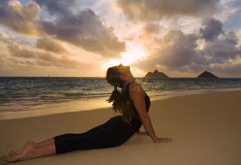 执行女子瑜伽年轻人的海滩 免版税库存图片