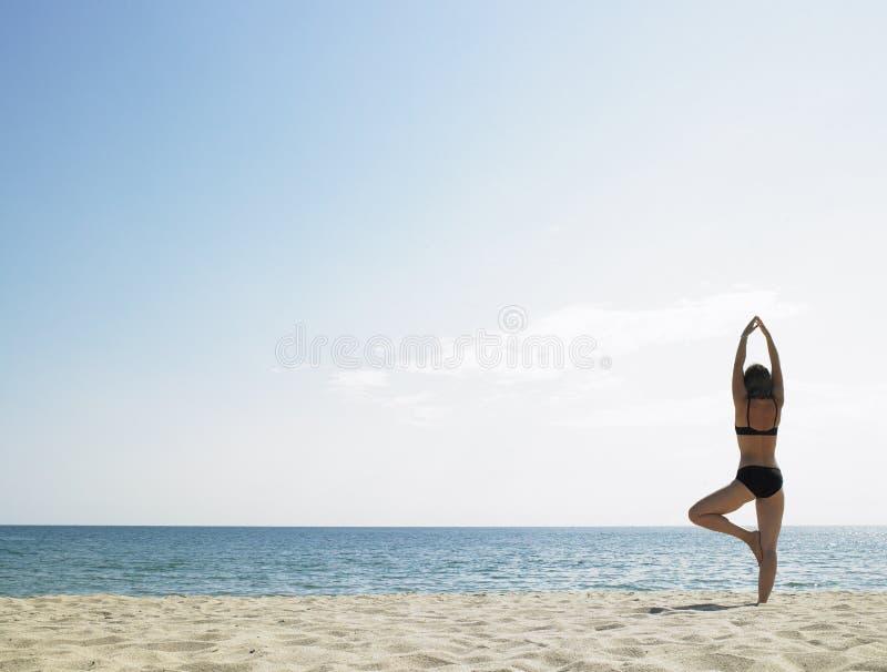 执行女子瑜伽的海滩 免版税图库摄影