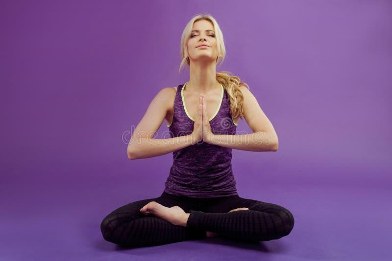 执行女子瑜伽 紫色背景的年轻运动的妇女 库存照片