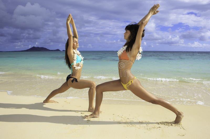执行女孩二瑜伽的海滩 免版税库存图片