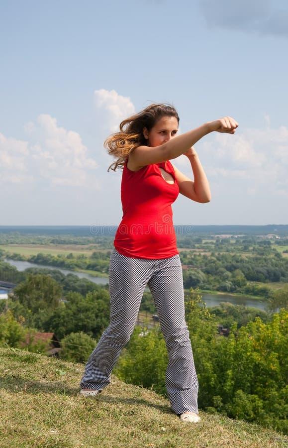 执行女孩kickboxing的本质年轻人 库存图片