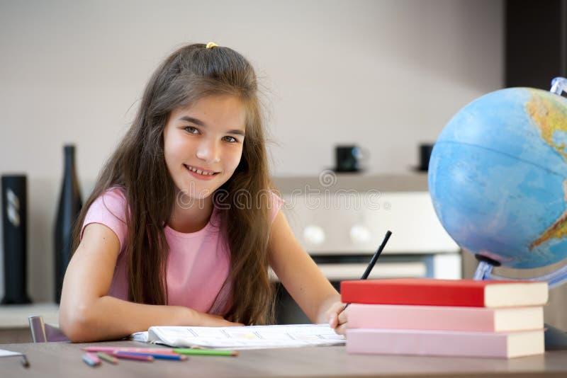 执行她的家庭作业的小女孩 免版税库存照片
