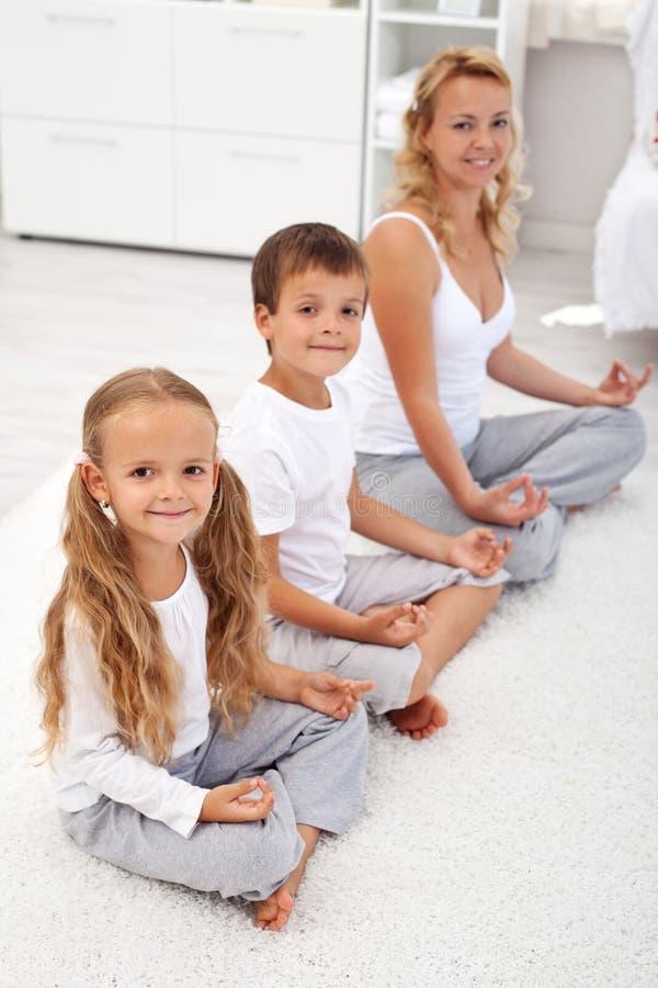 执行孩子照顾放松他们的瑜伽 免版税库存照片