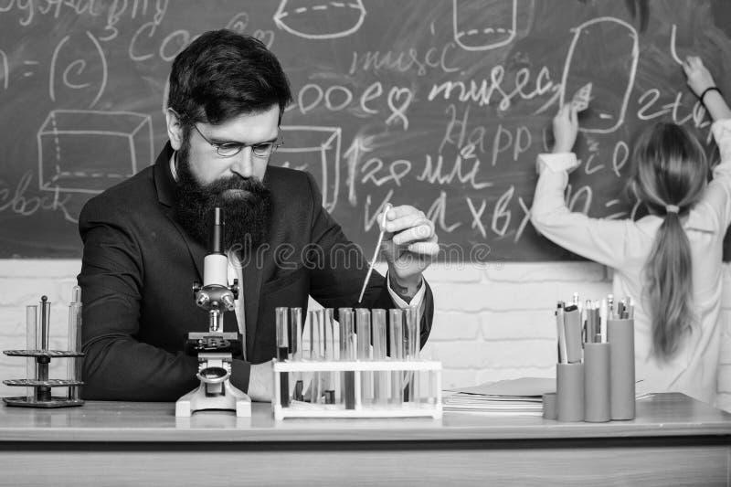 执行实验 老师和学生 教育的男老师在科学教室 公开或私立学校 免版税库存图片