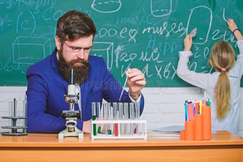 执行实验 老师和学生 教育的男老师在科学教室 公开或私立学校 免版税库存照片