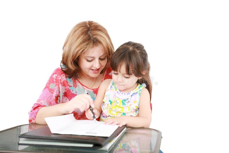 执行家庭作业的母亲和女儿 免版税库存照片