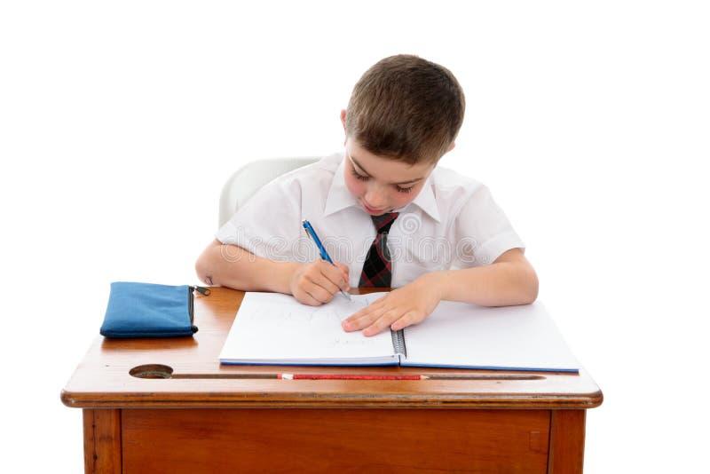 执行家庭作业的男孩一点学校工作 免版税库存照片