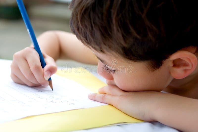 执行家庭作业的男孩户外 免版税库存照片