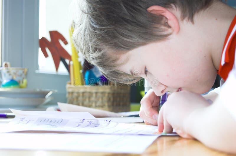 执行家庭作业的男孩 免版税图库摄影