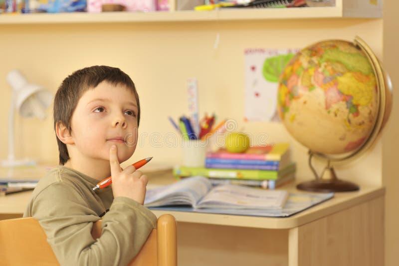 执行家庭家庭作业的男孩 库存照片