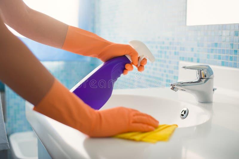 执行差事的妇女在家清洗卫生间 免版税库存照片