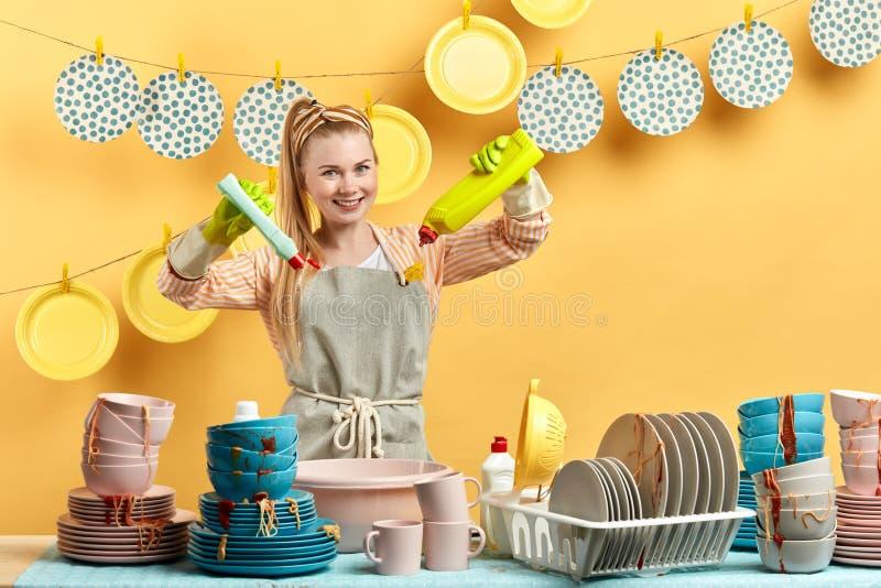 执行手洗涤物的宜人的正面白肤金发的妇女 免版税库存图片