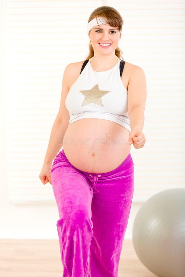 执行执行怀孕的微笑的妇女的有氧运&# 免版税库存照片