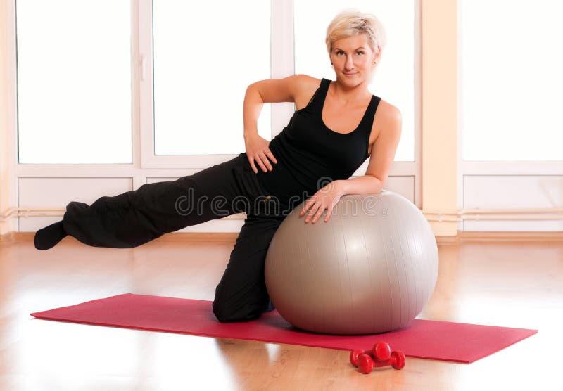 执行执行适合的健身妇女年轻人的球 库存照片