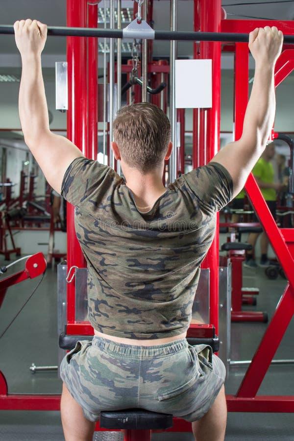 执行拉特折叠式的人在健身房 免版税图库摄影