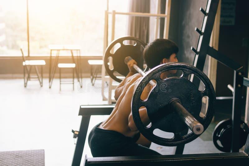 执行杠铃蹲坐的亚裔人在室内健身房 免版税图库摄影
