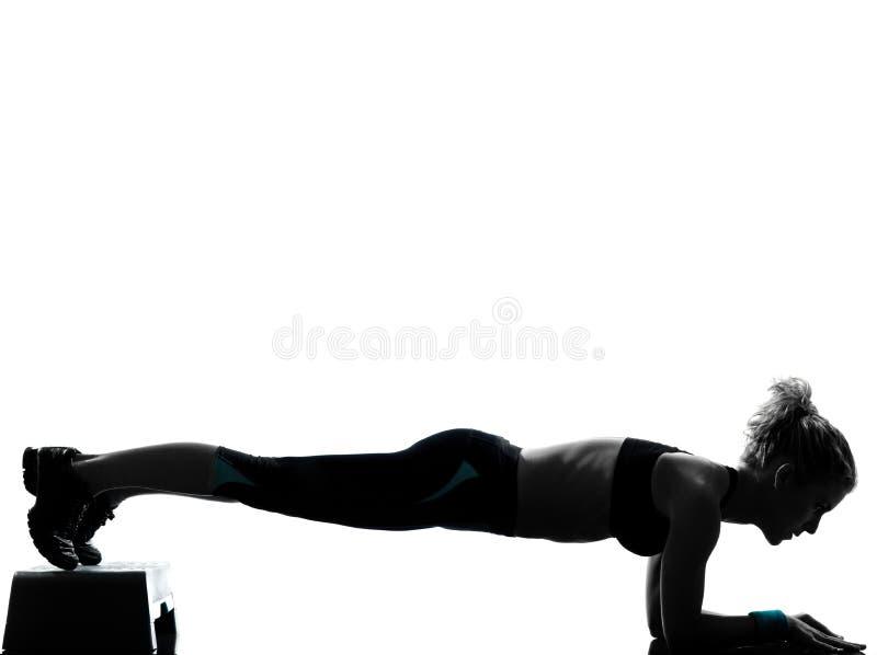 执行步骤有氧运动俯卧撑的妇女 免版税库存图片