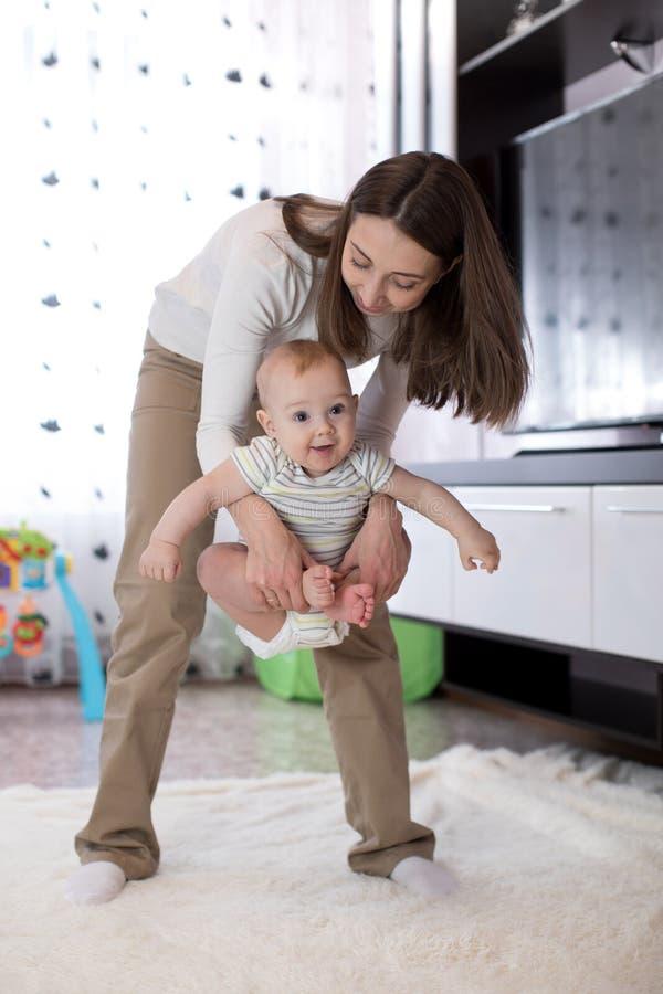 执行母亲瑜伽的婴孩 免版税库存图片