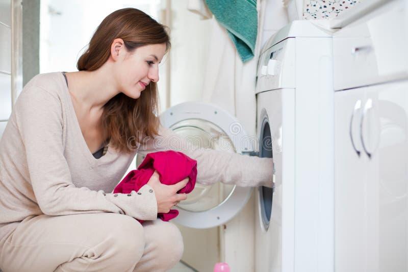 执行洗衣店的家事少妇 免版税库存照片