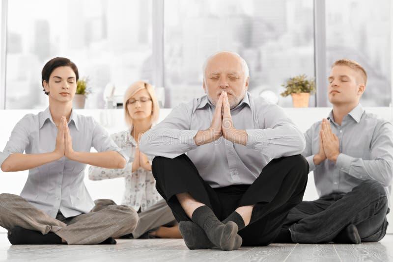 执行瑜伽凝思的Businessteam 免版税库存图片
