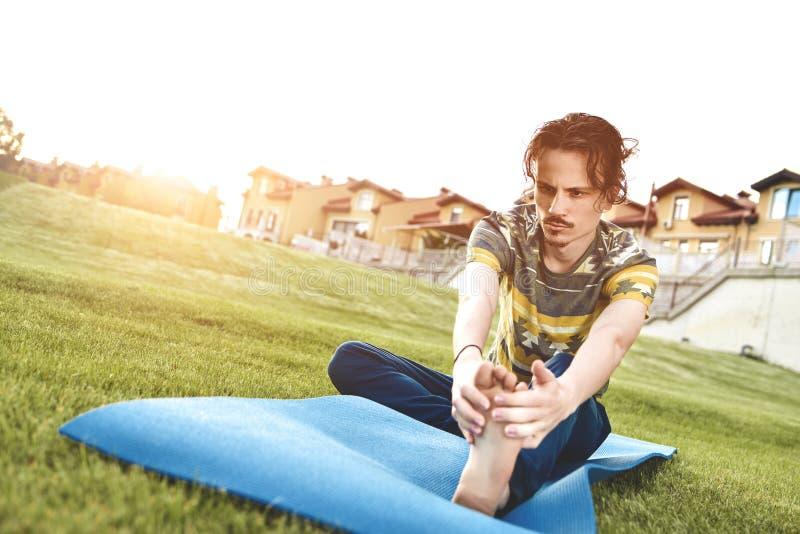 执行瑜伽年轻健身人室外做的锻炼的人 腿舒展 免版税图库摄影