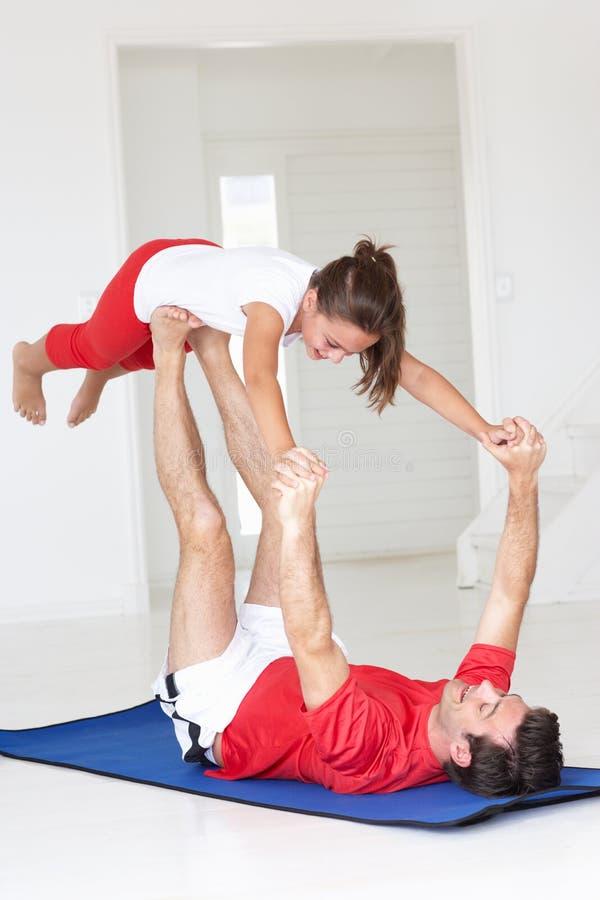 执行瑜伽推力的父亲和女儿 免版税库存照片