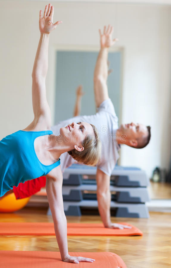 执行瑜伽的夫妇 免版税库存图片