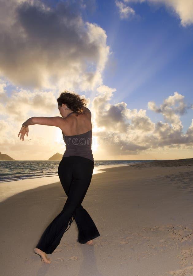 执行瑜伽的少妇在海滩 免版税图库摄影