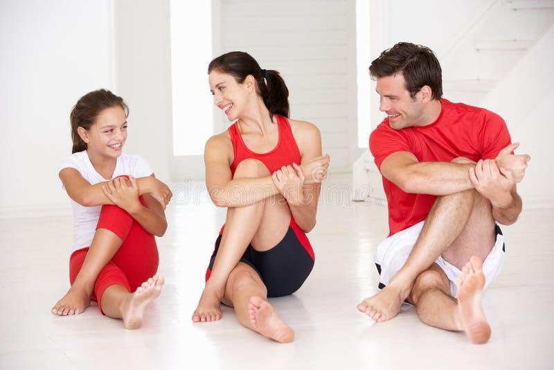 执行瑜伽的母亲、父亲和女儿 免版税库存图片