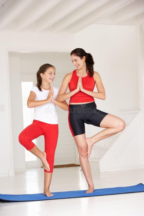 执行瑜伽的母亲和女儿 免版税库存图片