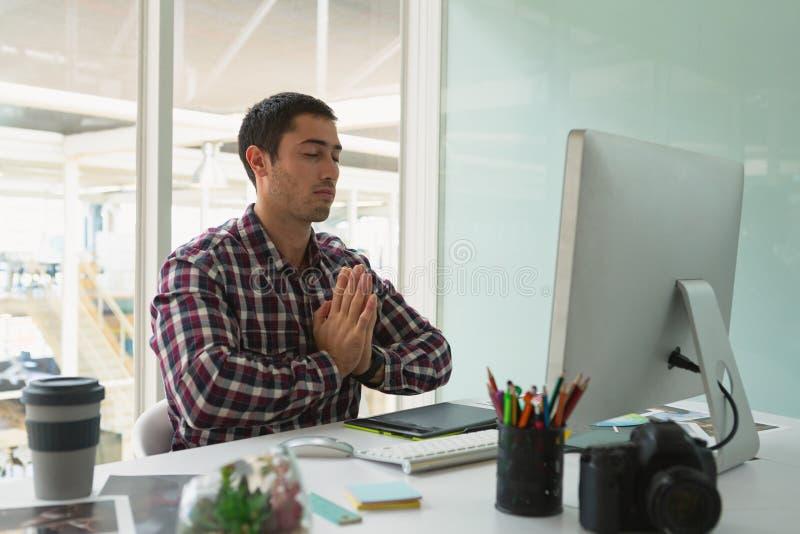 执行瑜伽的男性图表设计师在书桌 免版税库存图片