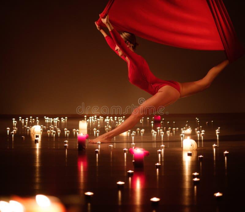 执行空中瑜伽的红色的女孩在松弛蜡烛点燃 免版税图库摄影