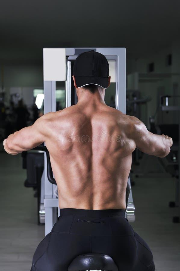 执行背部锻炼的英俊的强有力的运动人 免版税图库摄影