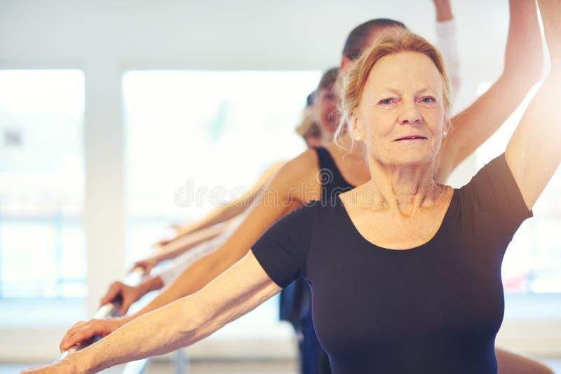执行芭蕾的资深妇女看照相机 免版税图库摄影