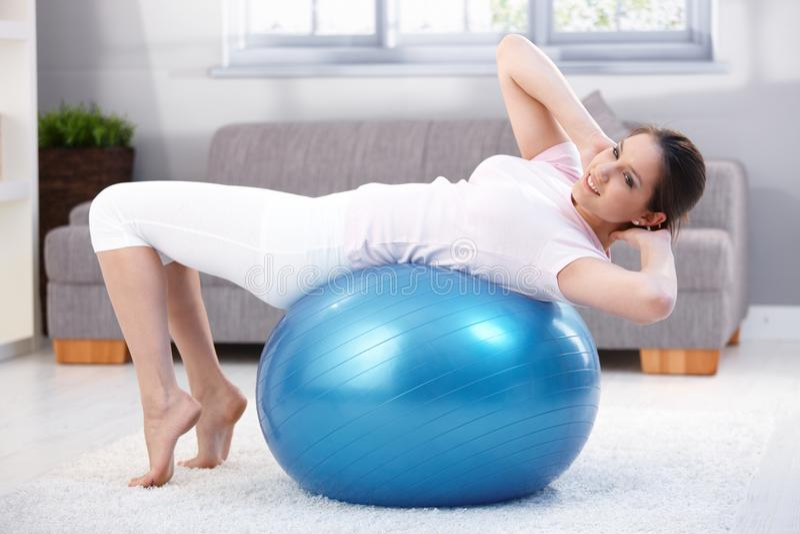 执行适合球锻炼微笑的少妇 免版税库存图片