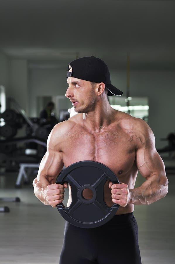 执行静态锻炼的英俊的强有力的运动人与重量 免版税库存照片