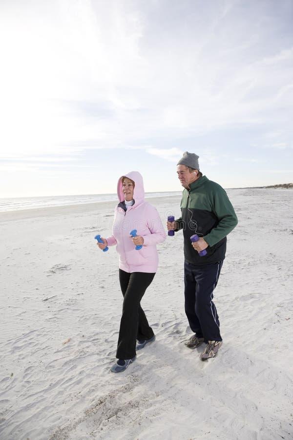 执行高级走的海滩夫妇 库存图片
