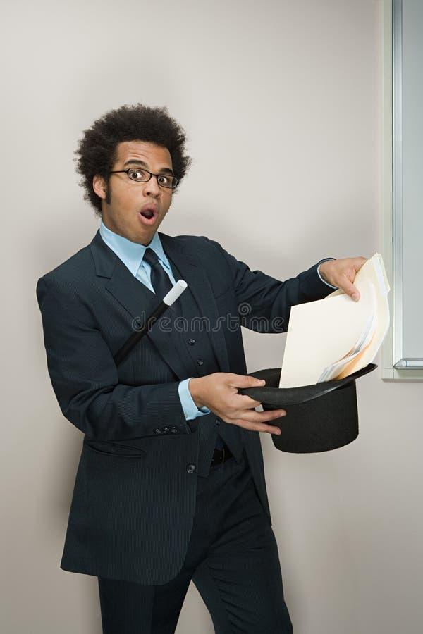 执行魔术技巧的商人 库存照片