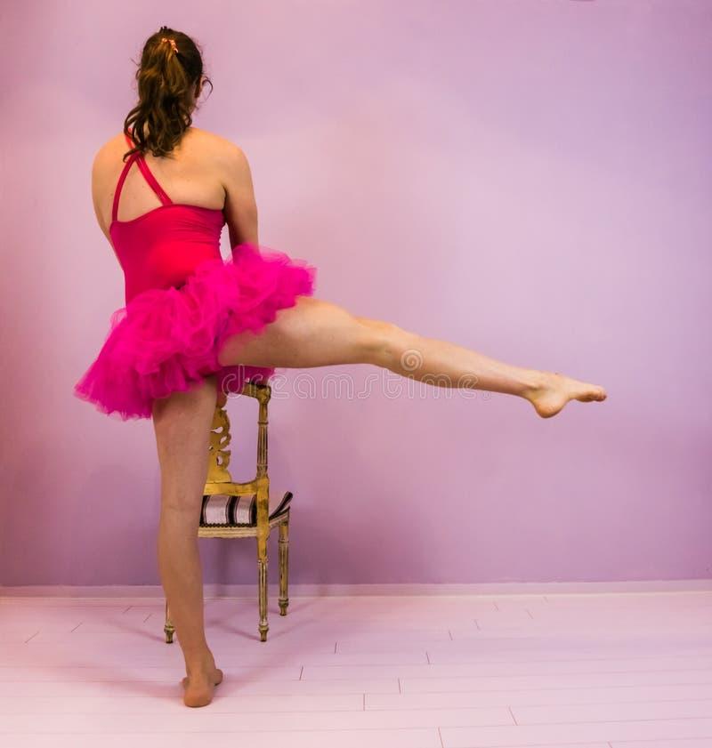 执行developpe,古典芭蕾移动,从后面的看法的芭蕾舞女演员,执行由一个年轻变性女孩 免版税库存照片