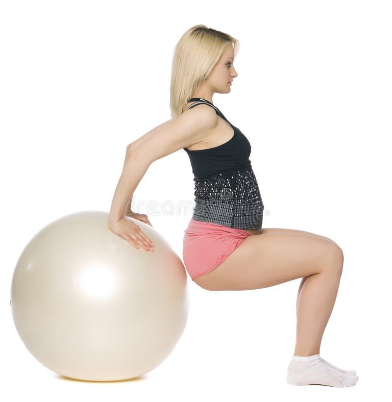 执行pilates的白肤金发的孕妇。 免版税库存图片