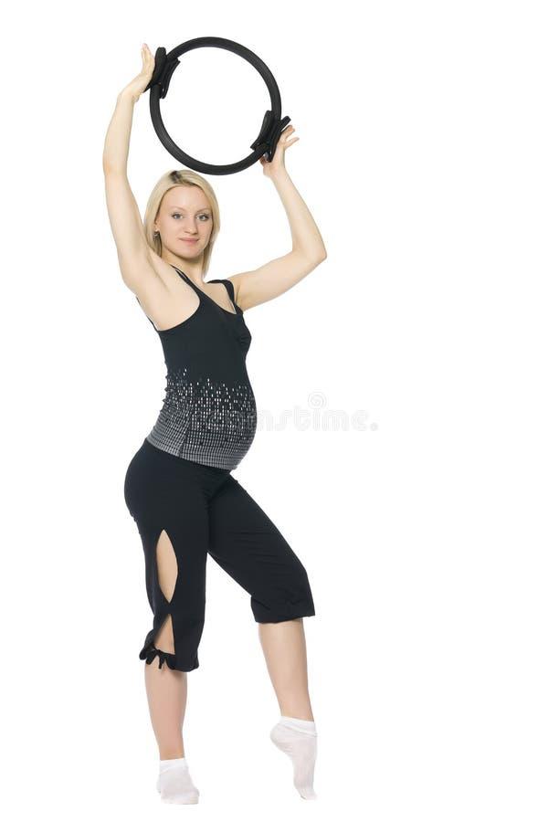 执行pilates的白肤金发的孕妇。 库存图片